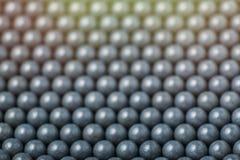 Suddig bakgrund av gråa airsoftbollar av 6mm Arkivbilder