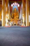 Suddig bakgrund för guld- Buddhastaty Arkivbild