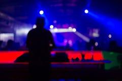 Suddig bakgrund: Klubba diskodiscjockey som spelar och blandar musik för folkmassan av lyckligt folk Uteliv konsertljus arkivbilder