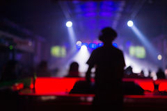 Suddig bakgrund: Klubba diskodiscjockey som spelar och blandar musik för folkmassan av lyckligt folk Uteliv konsertljus royaltyfria foton
