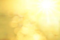 Suddig bakgrund med den guld- linsen blossar en sol Royaltyfria Bilder