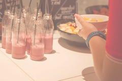 Suddig bakgrund med uppsättningen av smoothieexponeringsglas och flickahanden Royaltyfri Foto