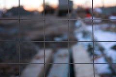 Suddig bakgrundskonstruktion till och med en metallskyddsgaller Arkivbild