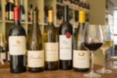Suddig bild av en rad av fem vinflaskor och vinglas Royaltyfri Bild