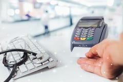 Suddig bild av räknareservice i sjukhus och betala med en kreditkort och använda en terminal Arkivfoto