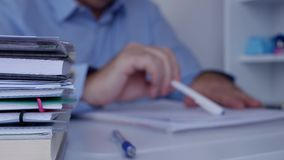 Suddig bild med affärsmannen Reading en dokumentation med blyertspennan i hand lager videofilmer