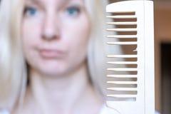 Suddig blond kvinna med en bruten hårkam i hennes hand fotografering för bildbyråer