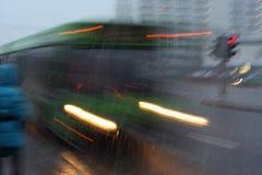 Suddig buss för rörelse på skymning i omilt väder Royaltyfria Bilder
