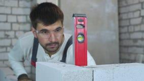 Suddig byggnadsarbetare som kontrollerar evenness av väggen med bubblanivån lager videofilmer