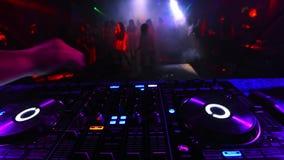 Suddig dansa folkmassa av folk i en nattklubb på partiet med en discjockeymusikblandare stock video