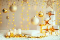 Suddig dekorera sammansättning för jul Julgåvor med det guld- bandet, kudden, den stack filten, julbollar och stjärnor Arkivbild