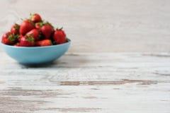 Suddig effektbakgrund Högen av saftiga mogna organiska nya jordgubbar i en stor blått bowlar Ljus lantlig träbakgrund royaltyfri foto