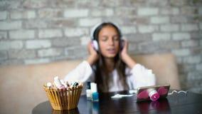 Suddig flicka i hörlurar som sjunger lyssnande musik på telefondanandemanikyr med utrymme för fri kopia stock video