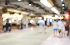 Suddig fotokvinnahemmafru med vagnsshopping i supermarket Royaltyfria Bilder