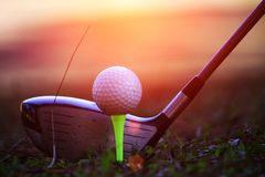 Suddig golfklubb och golfboll som är nära upp i gräsfält med solen royaltyfria bilder
