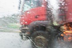 Suddig kontur av lastbilen som kör på vägen Synlighet igenom Royaltyfria Bilder