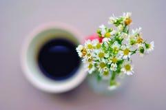 Suddig kopp kaffe och blommor Arkivfoton