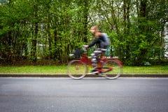 Suddig kvinnlig cyklist för rörelse på en stadsgata Arkivbild