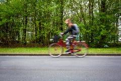 Suddig kvinnlig cyklist för rörelse på en stadsgata, Arkivbild