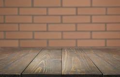 Suddig och abstrakt bakgrund Tom trätabletop och defocused bakgrund för tegelstenvägg för skärm dina produkter Royaltyfri Bild