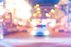 Suddig polisbil på gatan på natten Arkivfoton