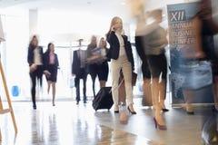 Suddig rörelse av affärsfolk med bagage som går på konventcentret Fotografering för Bildbyråer
