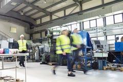 Suddig rörelse av affärsfolk som bär reflekterande kläder som går i metallbransch arkivbilder