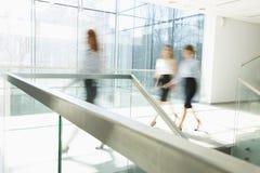 Suddig rörelse av affärskvinnor som går på kontorshallet arkivbilder