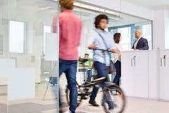 Suddig rörelse av kollegor med affärsfolk som diskuterar i bakgrund på kontoret Royaltyfri Foto