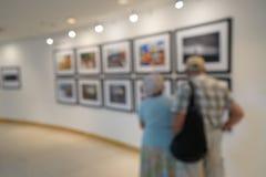 Suddig sikt av folk som ser bilden på väggen i utställningkonstgalleri fotografering för bildbyråer