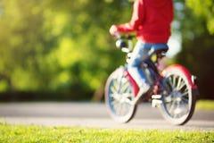 Suddig sikt till ett barn på en cykel på asfaltvägen royaltyfri fotografi
