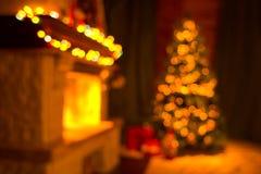 Suddig vardagsruminre med spisen och det dekorerade julträdet royaltyfri foto