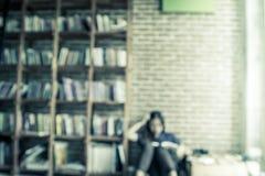 Suddiga böcker på hyllan med folk läser en bok Arkivfoton
