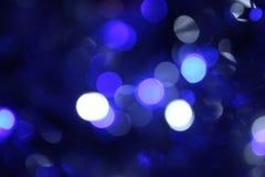 Suddiga bakgrundsljus blinkar bokeh på blå bakgrund Arkivbild
