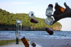 Suddiga händer som skräpar ner flaskan på stranden Arkivbild