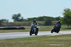 Suddiga idrottsman nen som öva tävlings- motorcyklar på loppspåret Arkivfoto
