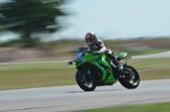 Suddiga idrottsman nen som öva tävlings- motorcyklar på loppspåret Royaltyfri Foto
