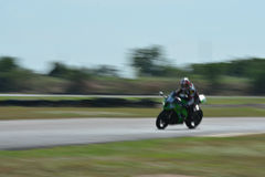 Suddiga idrottsman nen som öva tävlings- motorcyklar på loppspåret Fotografering för Bildbyråer