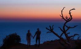 Suddiga konturer av händer för ett parinnehav på en solnedgånghavsbakgrund Arkivbilder