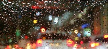 Suddiga medelsvanslampor som beskådas till och med vattensmå droppar på bilvindrutan royaltyfria foton