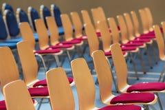 Suddiga rader av tomma trästolar i en stor aula Töm stolar i konferenskorridor Inre mötesrum royaltyfria foton