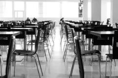 Suddiga rader av trätabeller och plast-stolar i restaurangen Arkivbild