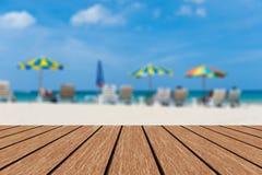 Suddiga strandstolar och paraplyer slösar havs- & himmelbakgrund med tomt trä Arkivbild