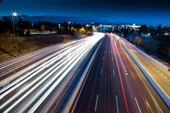Suddiga svansljus och trafikljus på motorwayen Arkivfoto
