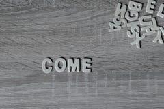 suddighet bakgrund Bokstäver på trätabellen ` Kommer `, Royaltyfri Fotografi