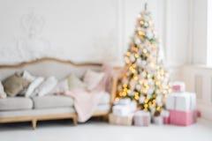 suddighet bakgrund Den lyxiga vardagsruminre med soffan dekorerade den chic julgranen, gåvor, plädet och kuddar Arkivfoton