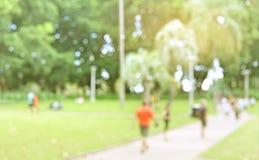 Suddighetsbakgrund av folk utarbetar i parkera Suddighet av folk w arkivfoton