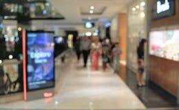 Suddighetsbakgrundsköpcentrum med folk som inom går blurriness arkivfoto