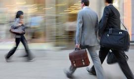 Suddigt affärsfolk för rörelse som går på gatan Arkivbild