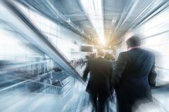 Suddigt affärsfolk som använder en rulltrappa på en handelmässa/mes Fotografering för Bildbyråer